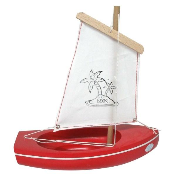petit bateau en bois à voile blanche avec une coque de couleur rouge