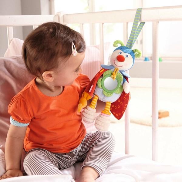 La coccinelle Juju à suspendre accrochée sur un lit à barreau avec un enfant qui joue avec