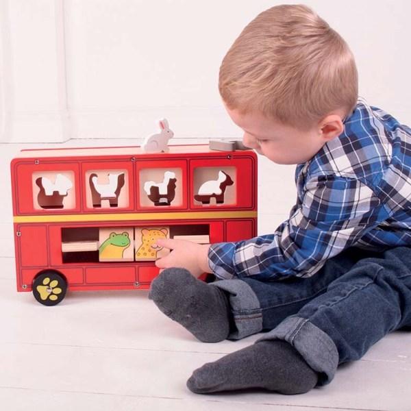 un enfant joue avec la Boîte à formes Bus des animaux