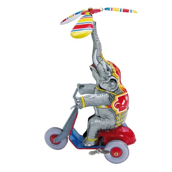 Éléphant en métal à remonter sur un scooter avec un objet en équilibre au dessus de sa trompe