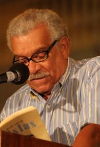 Photo of poet Derek Walcott reading at a microphone.