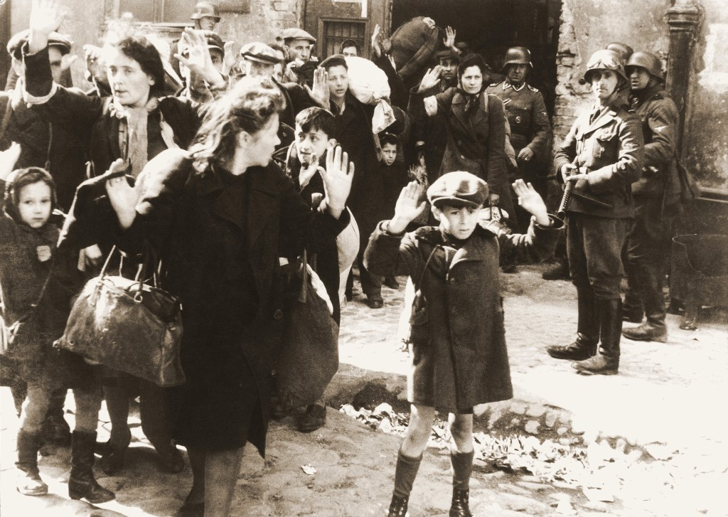 Photo showing women and children with their hands raised in front of Nazi soldiers with guns in the Warsaw ghetto during World War II.