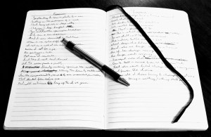 Photo of an open notebook with writing in it and a pen laying on top.