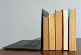 Photo of an open laptop and a stack of books on a desk.