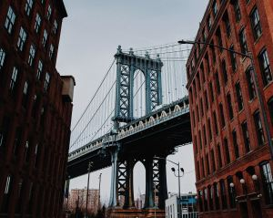 Photo of the Brooklyn Bridge between two brick buildings.