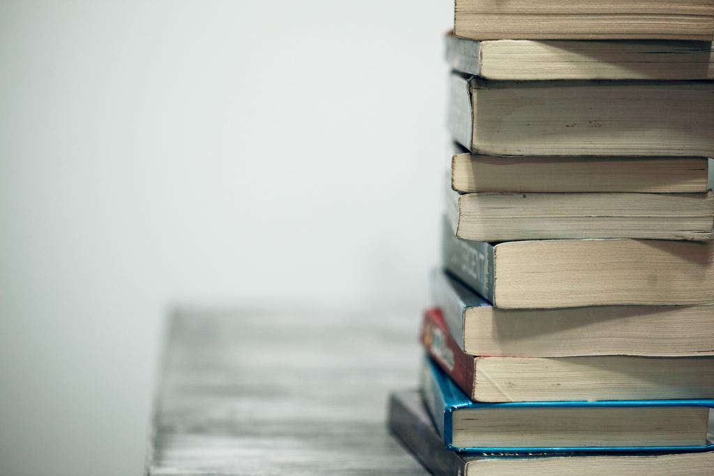 Photo of a stack of books sitting on a table.
