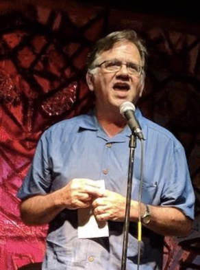 poet Chuck Joy speaking at a microphone.
