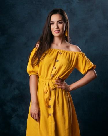 Małgosia wżółtej sukience naniebieskim tle.