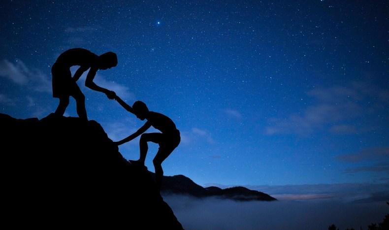 un homme aide un autre à gravir une montagne effet Pygmalion