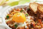 Deliciosos huevos al plato con berenjena y tomate