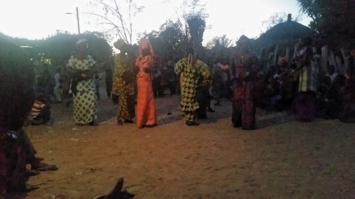 Women dancing at a Baptism as night falls