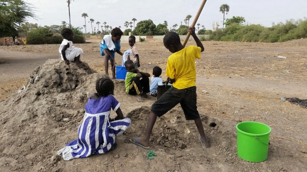 Local children helping to harvest clay from a nearby termite mound to use for my mud oven