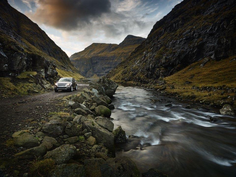 bil i natur med høye fjell og bekk