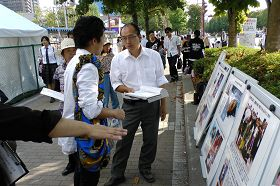 日本東廣島市第二十三屆酒節上,遊客聽法輪功學員講真相