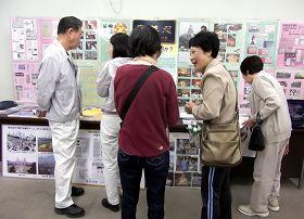 '前來參加活動的民眾有的觀看真相圖片展,有的傾聽學員介紹大法真相。'