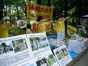 法輪功學員在稻澤市第十七屆夏季活動節展位上煉功