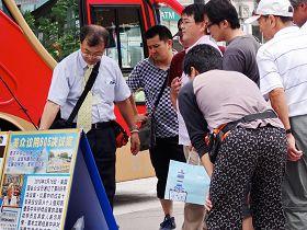 '日本導遊正向他的團員解說展板上法輪功學員被中共迫害的事實真相'
