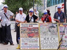 '遊客們聚集在展板前了解法輪功真相'