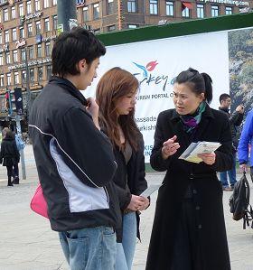法輪功學員在向過往的世人介紹法輪大法及發生在中國的邪惡迫害