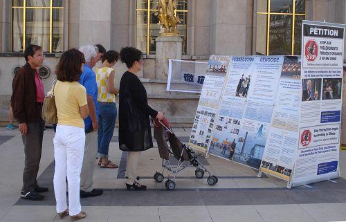 巴黎人權廣場上,民眾閱讀展板,了解法輪功真相