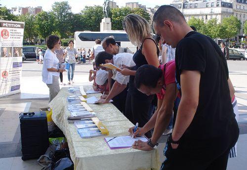 巴黎人權廣場上,人們簽名譴責中共活摘器官