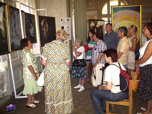 圖:烏克蘭哈爾科夫市的真善忍美展上,觀眾欣賞畫作,聆聽導覽。