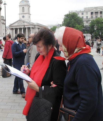 '兩位移居倫敦的波蘭女士互相鼓勵在反迫害徵簽表上簽名'