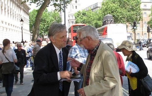 法輪功學員在英國首相府前,跟前來看熱鬧的人們講述法輪功的真相。