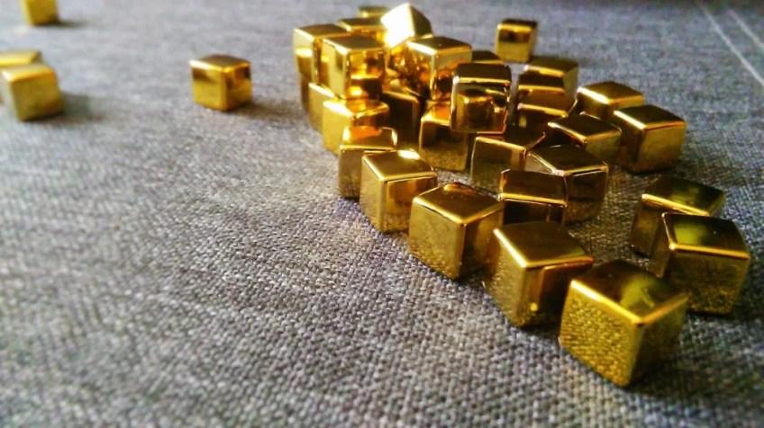 Tu mamy wspomniane już we wstępie metaliczne kosteczki. Występują w różnych kolorach: złoto, srebro brąz. Są to kostki zasobów, w pudełku łącznie jest ich 200.