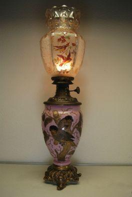 Lamparín estilo art nouveau. El fanal es de cristal Baccart color ambar y decorado a mano con diseno de pájaros. La base es de cristal opalina rosada que esta decorada con pájaros en pan de oro y en alto relieve. Francia 1890.