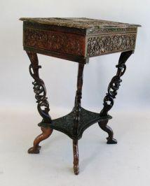 Mesa de coser indoamericana en madera ébano y tallada profusamente. USA principios del siglo XIX.