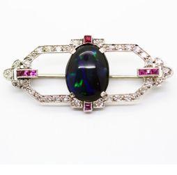 Delicado broche Art Decó de oro blanco. Tiene diamantes incrustados, rubíes y un gran ópalo negro al centro.
