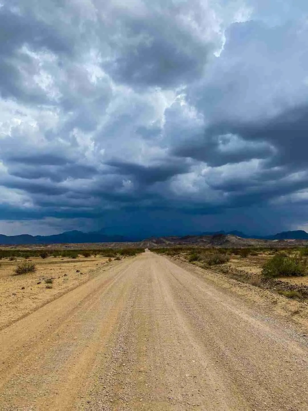 Old Maverick Road with storm over chisos