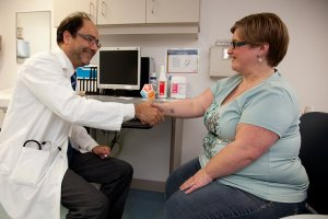 Plus-size friendly professional meeting a patient with a smile and a handshake