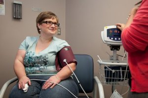 Plus-Size Friendly Professional -Woman smiling having her blood pressure checked.