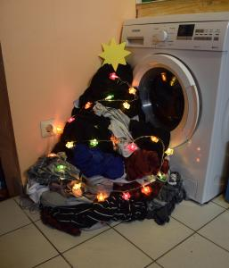Pile of laundry by a washing machine, decorated with lights and star to look like a Christmas tree. Festive fashion if you're plus-size & pregnant