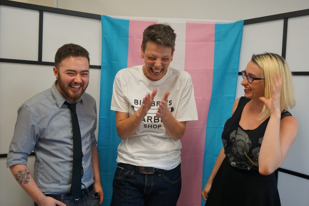 Jessie, Zed and Brianne laughing together in front of trans flag backdrop
