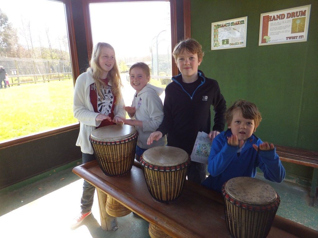Children playing bongos in a hut at Africa Alive