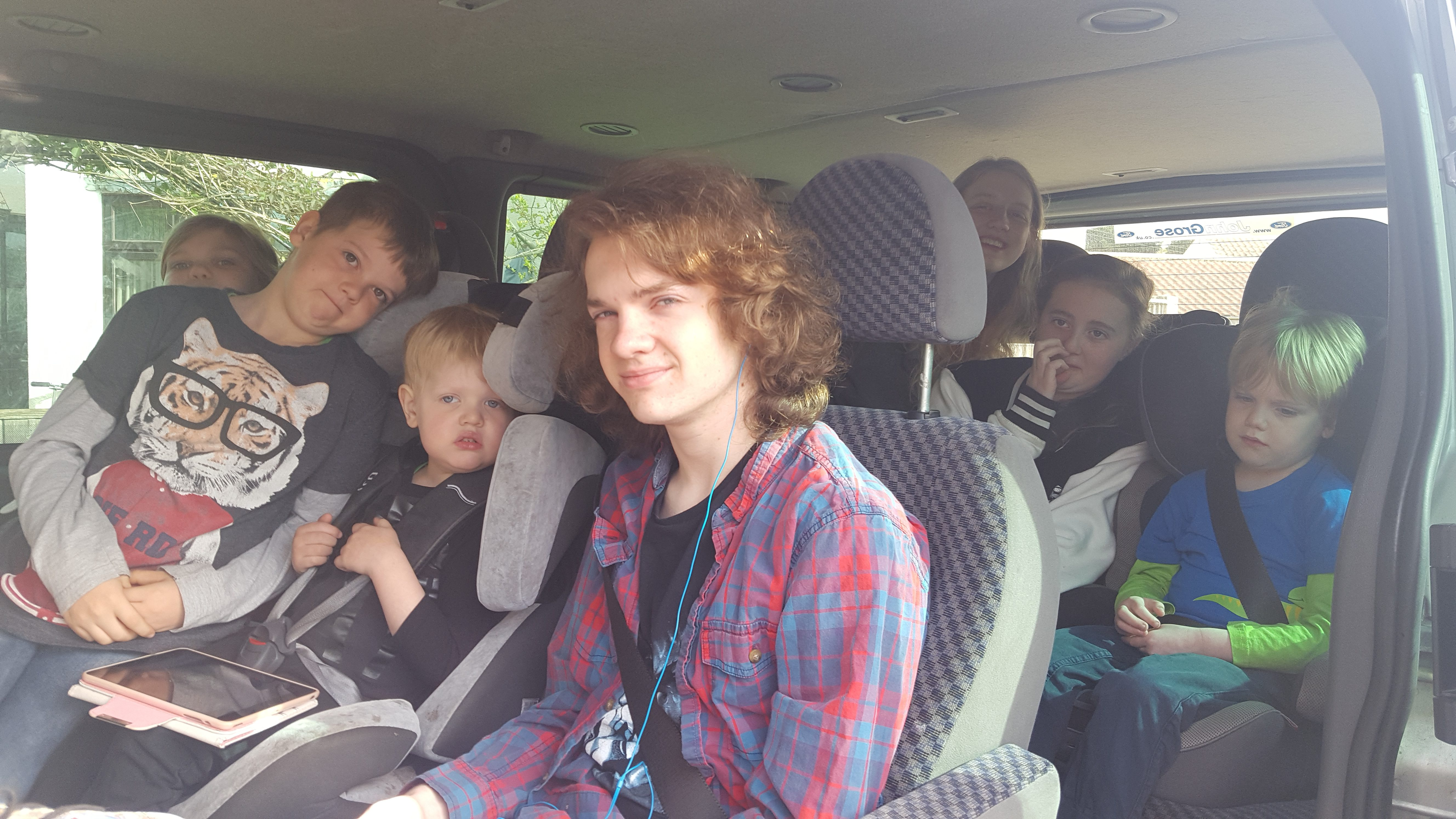 All seven children sitting in the car waiting to drive to the station