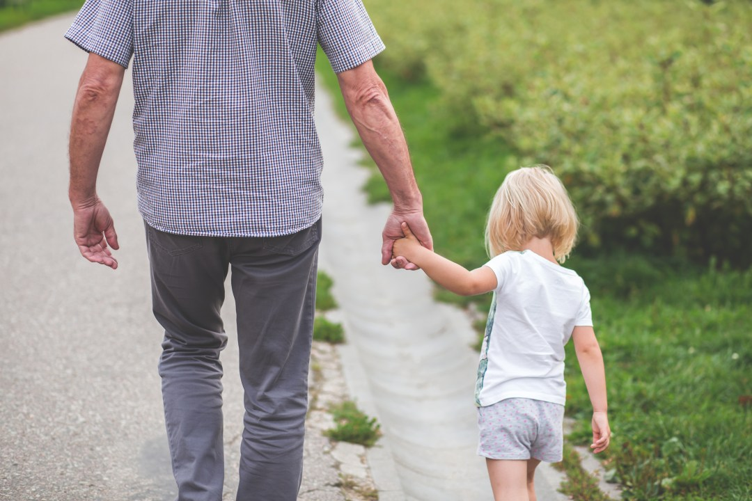 multi-generational travel - a grandfather holding hands with his granddaughter