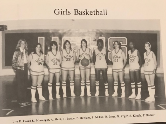 Black and white picture of the Union County High School girls basketball team. The coach is in a shiny jacket and the players are in shorts, sleeveless tops and knee socks. One player is holding a basketball.