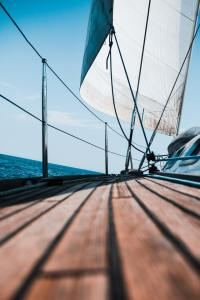 A sailboat with a wooden deck and white sail overlooking a dark blue ocean and light blue sky.