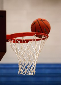 An orange basketball rim with a white net and an orange and black basketball sitting on the edge of the rim
