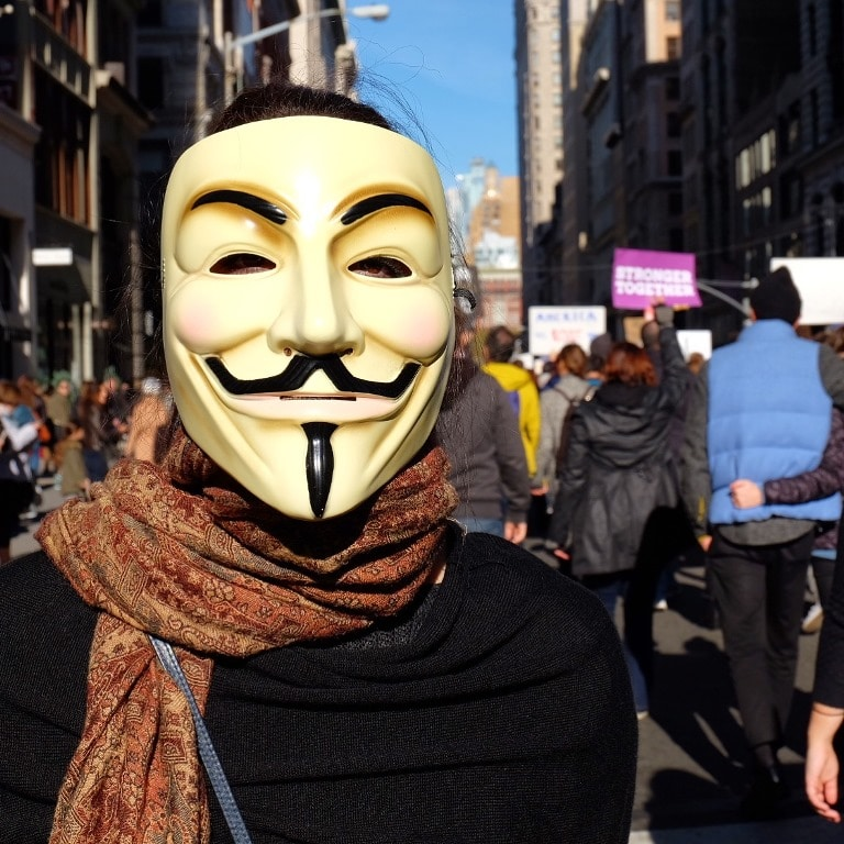 A protester wearing their Guy Fawkes mask - off to Trump Tower