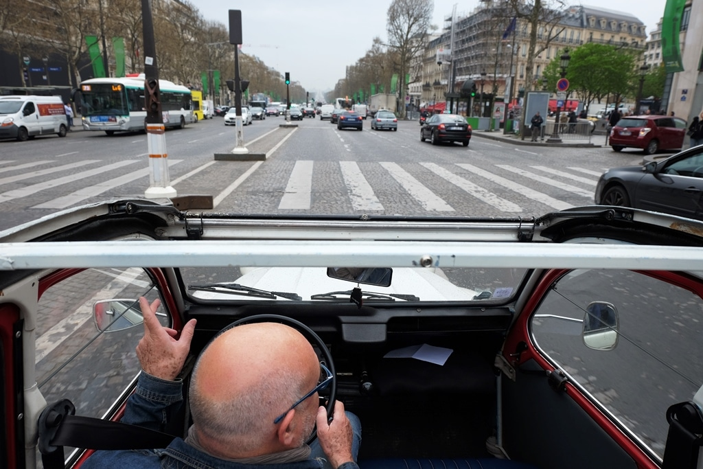Driving a 2CV down the Champs-Élysées with the roof down