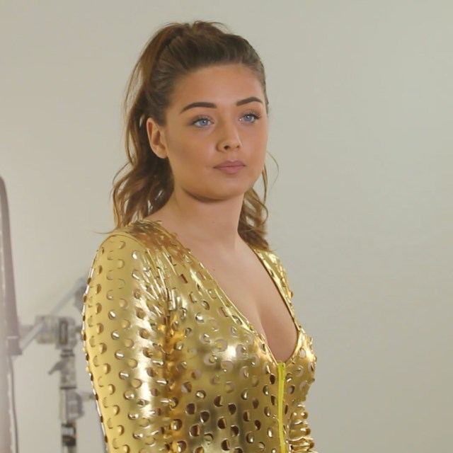 Miss England finalist Rheo in the studio wearing a gold catsuit