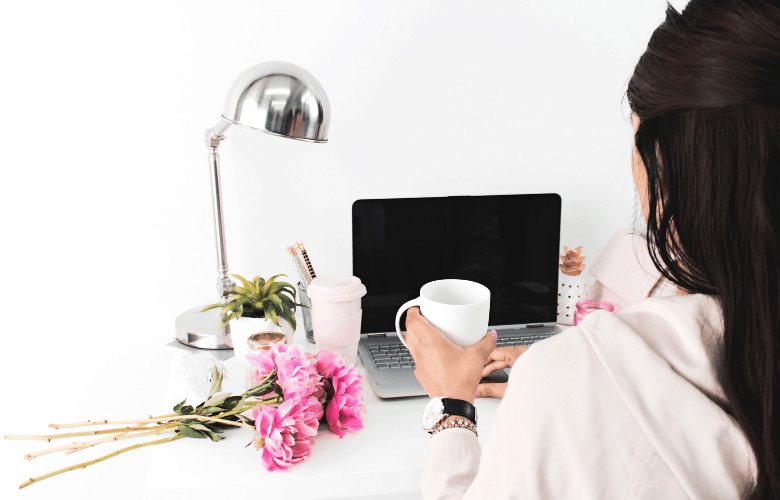 woman with coffee in front of her laptop and roses