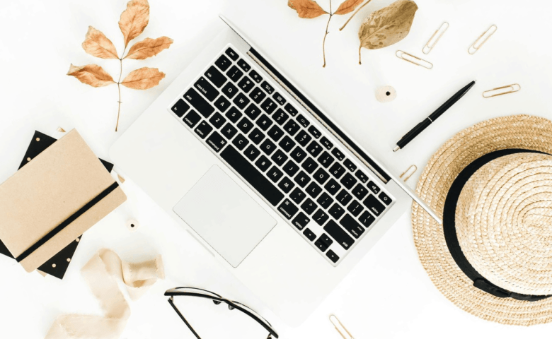 Autumn composition with laptop, dry autumn leaves and straw on white background. Flat lay, top view.