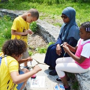 Four young people working on a project in a park.