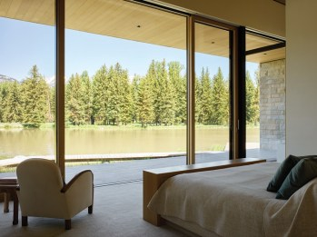 The spacious master bedroom opens to views of the water and the surrounding meadow.